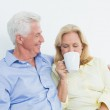 Senior couple with coffee cup sitting on sofa — Stock Photo