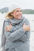 Cheerful senior woman shivering at beach — Stock Photo