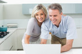 Happy couple using laptop in kitchen — 图库照片