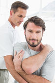 Male physiotherapist examining a young man — Stock Photo