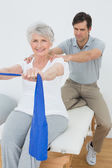 Male therapist assisting senior woman with exercises — Stock Photo