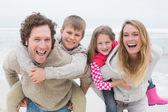 Paar meeliften kinderen op het strand — Stockfoto