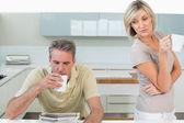 Casal com café xícaras lendo jornal na cozinha — Fotografia Stock