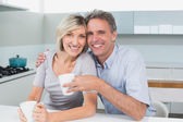 Happy loving couple with coffee cups in kitchen — Stock Photo