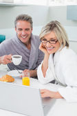 Couple in bathrobes with coffee and juice using laptop — Stock Photo