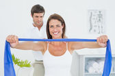 Male therapist assisting young woman with exercises — Stock Photo