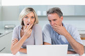 Shocked couple with laptop in kitchen — ストック写真