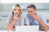 Casal chocado com o laptop na cozinha — Foto Stock