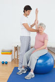 Senior woman on yoga ball with a physical therapist — Stock Photo
