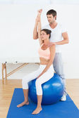 Woman on yoga ball working with physical therapist — 图库照片