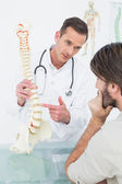 Male doctor explaining the spine to a patient — Stock Photo