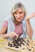Portrait of a woman playing chess at table — Stockfoto