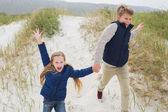 Happy siblings running hand in hand at beach — Stockfoto