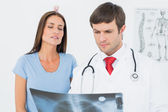 Male doctor explaining lungs x-ray to female patient — Stock Photo