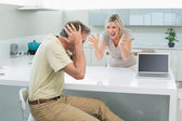 Man covering his ears as woman argue in kitchen — Foto de Stock