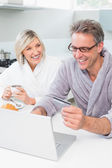 Couple in bathrobes using laptop in kitchen — Fotografia Stock