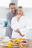 Man embracing a happy woman from behind in kitchen — Stock Photo