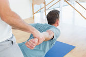 Therapist assisting man with stretching exercises — Stock Photo
