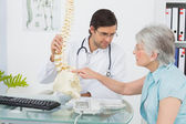 Male doctor explaining the spine to a senior patient — Stock Photo