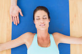Woman relaxing with eyes closed at hospital gym — Stok fotoğraf