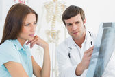 Male doctor explaining spine x-ray to female patient — Stok fotoğraf