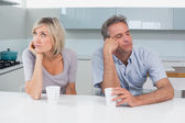 Displeased couple sitting with coffee cups in kitchen — Foto de Stock