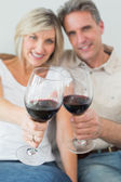 Happy couple holding out wine glasses — Stock Photo