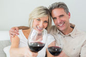 Couple holding out wine glasses at home — Stock Photo