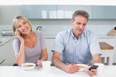 Couple reading text messages while having breakfast — Stock Photo