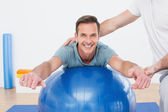 Physical therapist assisting young man with yoga ball — Stock Photo