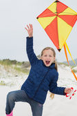 Cheerful young girl with kite at beach — Stock Photo