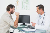 Male doctor in conversation with patient at desk — Stock Photo