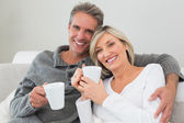 Relaxed happy couple with coffee cups in living room — Stock Photo