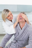 Woman covering a happy man's eyes in kitchen — Stockfoto