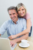 Content couple using laptop at home — Stock Photo