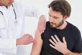 Male doctor injecting a young male patient's arm — Stock Photo
