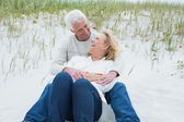 Romantic senior couple relaxing at beach — Stock Photo