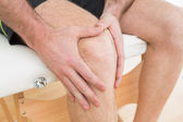 Mid section of a man with his hands on a painful knee — Stock Photo