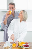 Man drinking orange juice and woman cutting fruits in kitchen — Stock Photo