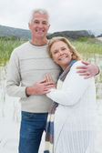 Happy senior man embracing woman at beach — Stock Photo