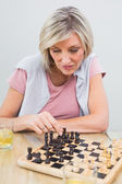 Concentrated woman playing chess at table — Stock Photo