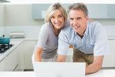 Portrait d'un couple heureux avec l'ordinateur portable dans la cuisine — Photo
