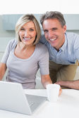 Happy casual couple using laptop in kitchen — Stock fotografie