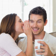 Woman whispering secret into a happy mans ear in living room — Photo #42585333