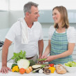 Happy couple preparing food together in kitchen — Stock Photo #42584769