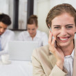 Businesswoman using mobile phone with colleagues at office desk — Stock Photo #42584775