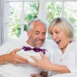 Mature man giving surprised woman gift box at home — Stock Photo
