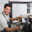 Smiling waiter making cup of coffee at coffee shop — Stock Photo #42584803