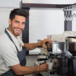 Smiling waiter making cup of coffee at coffee shop — Stock Photo