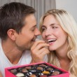 Relaxed happy couple eating candies — 图库照片